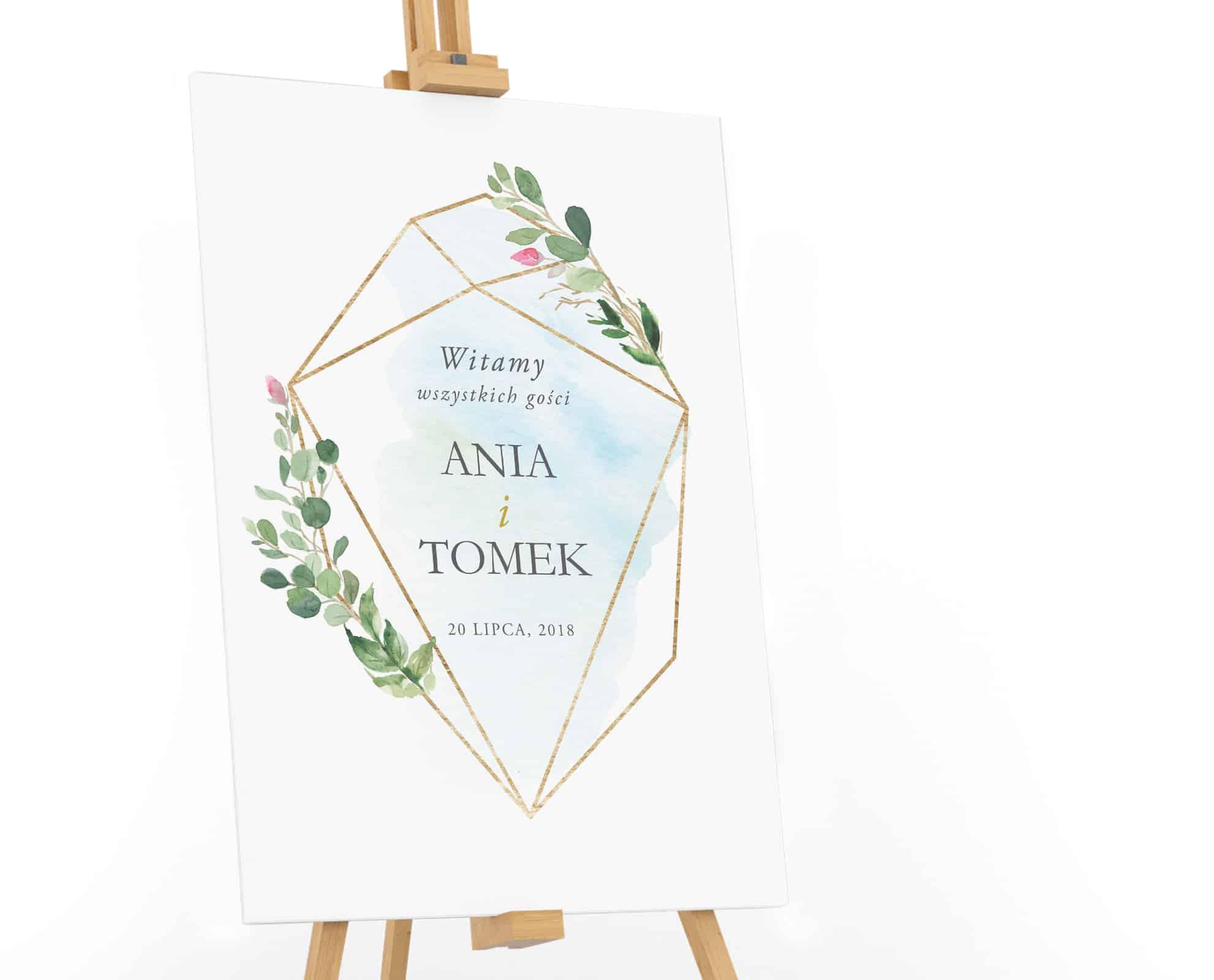 Tablica powitalna dla gości weselnych ze złotą figurą geometryczną i niebieskim tłem