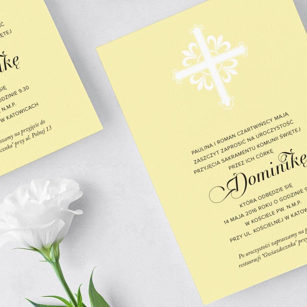 Żółte zaproszenie z białym ozdobnym krzyżem i ładną czcionką