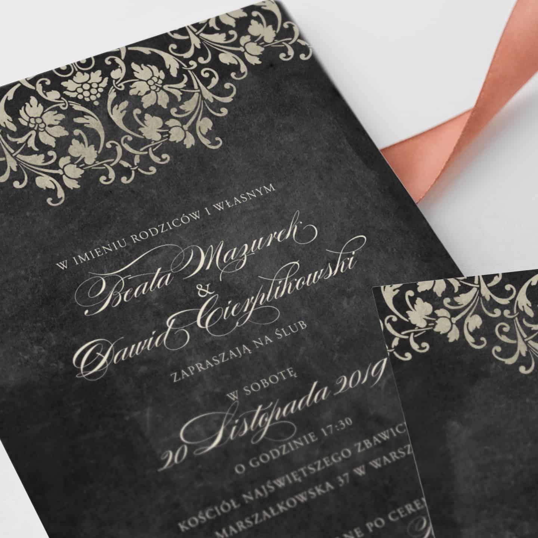 Zaproszenie w kolorze czarnym ze zdobieniami w kolorze starego złota i ozdobnym pismem