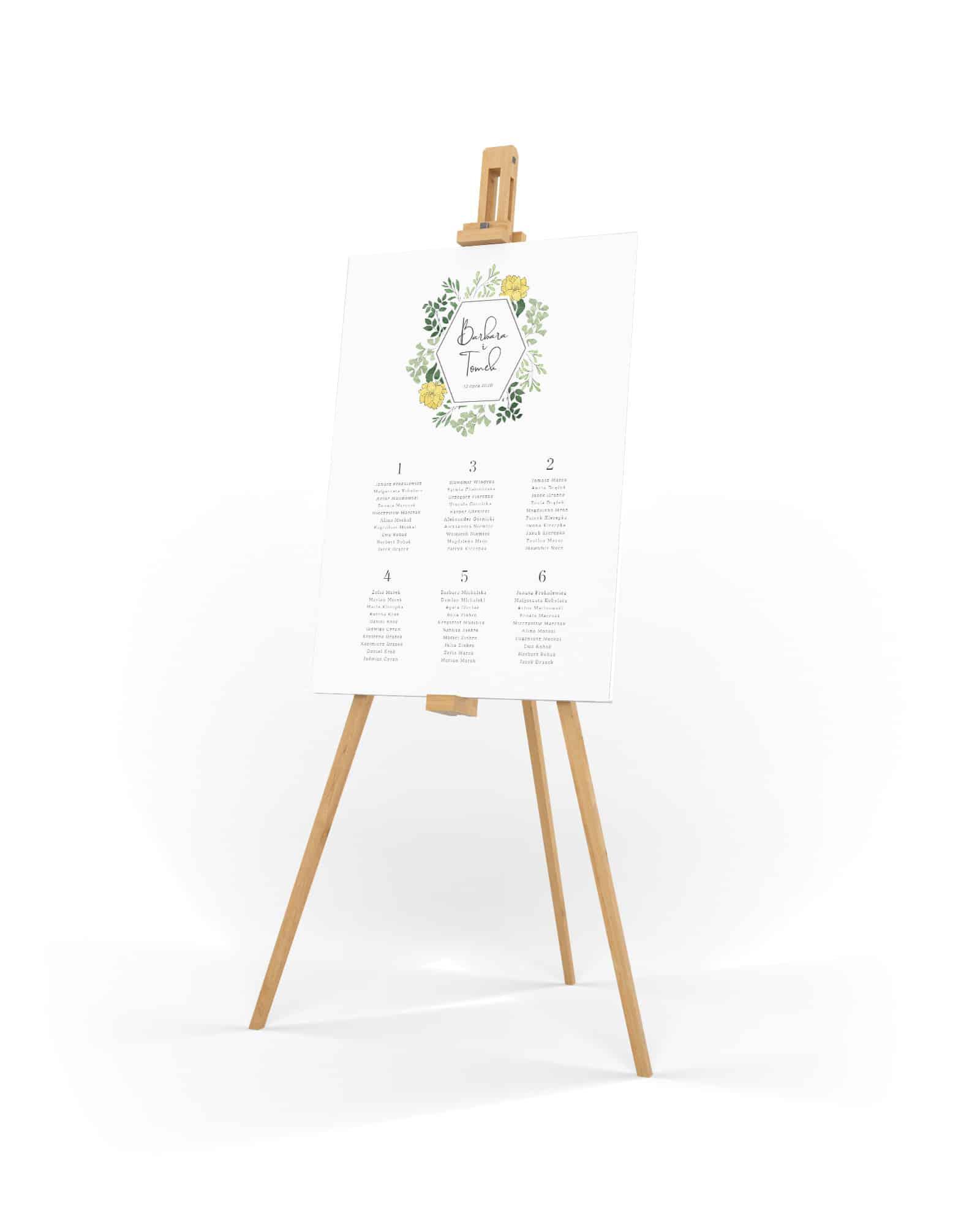 Prosty i elegancki plan stołów z małymi zielonymi listkami dookoła imion Pary Młodej