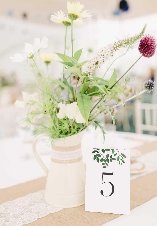 Numery na stoły ładne i przejrzyste z zielonymi gałązkami