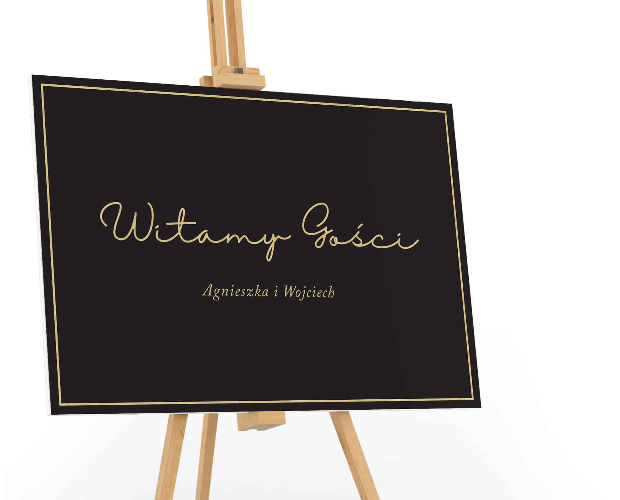 Czarna tablica powitalna ze złotym napisem witamy gosci