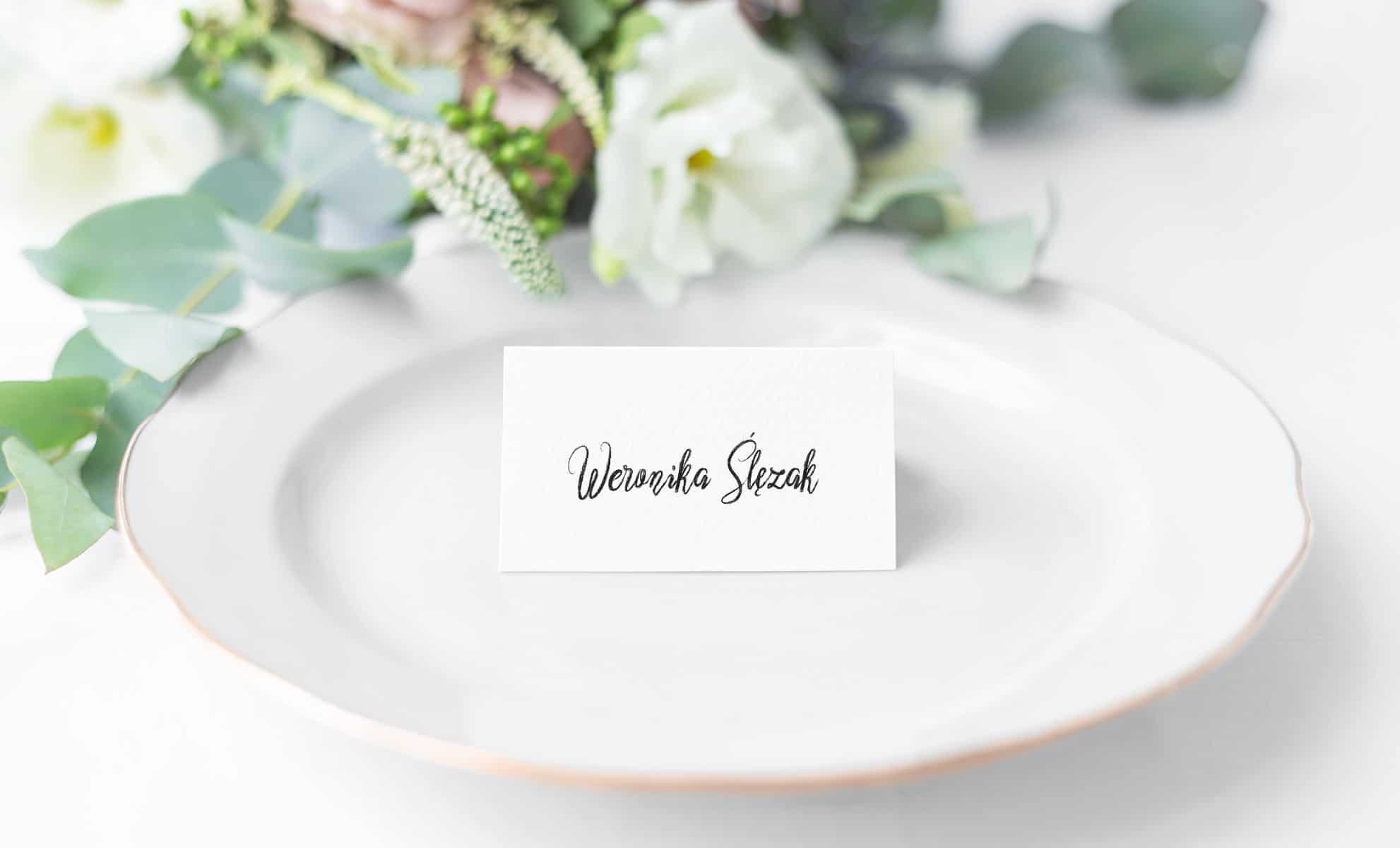 minimalistyczne białe winietki z imionami gości wypisanymi ozdobną czcionką