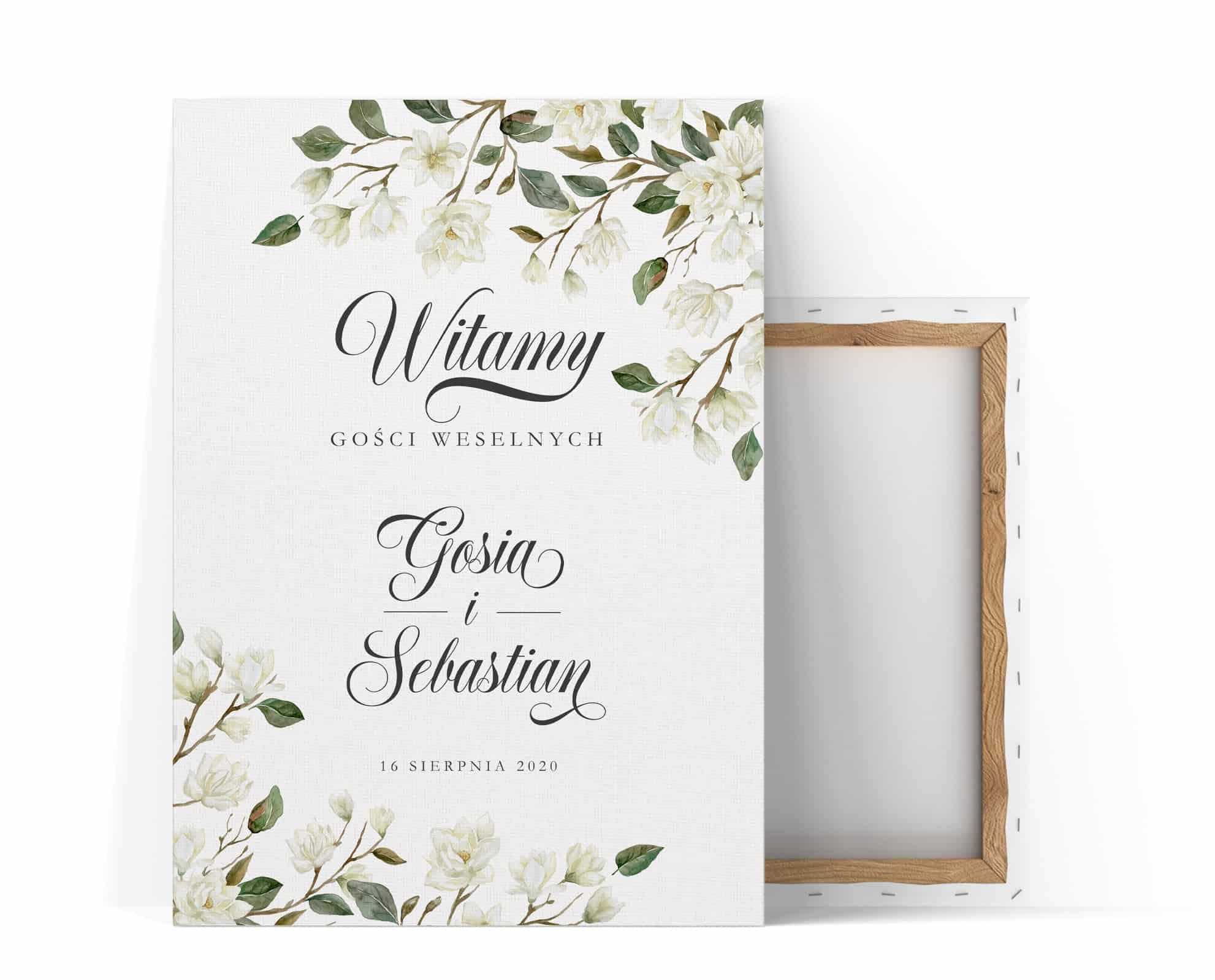 Tablica powitalna gości na uroczystości z dużą ozdobną czcionką i kompozycją magnolii