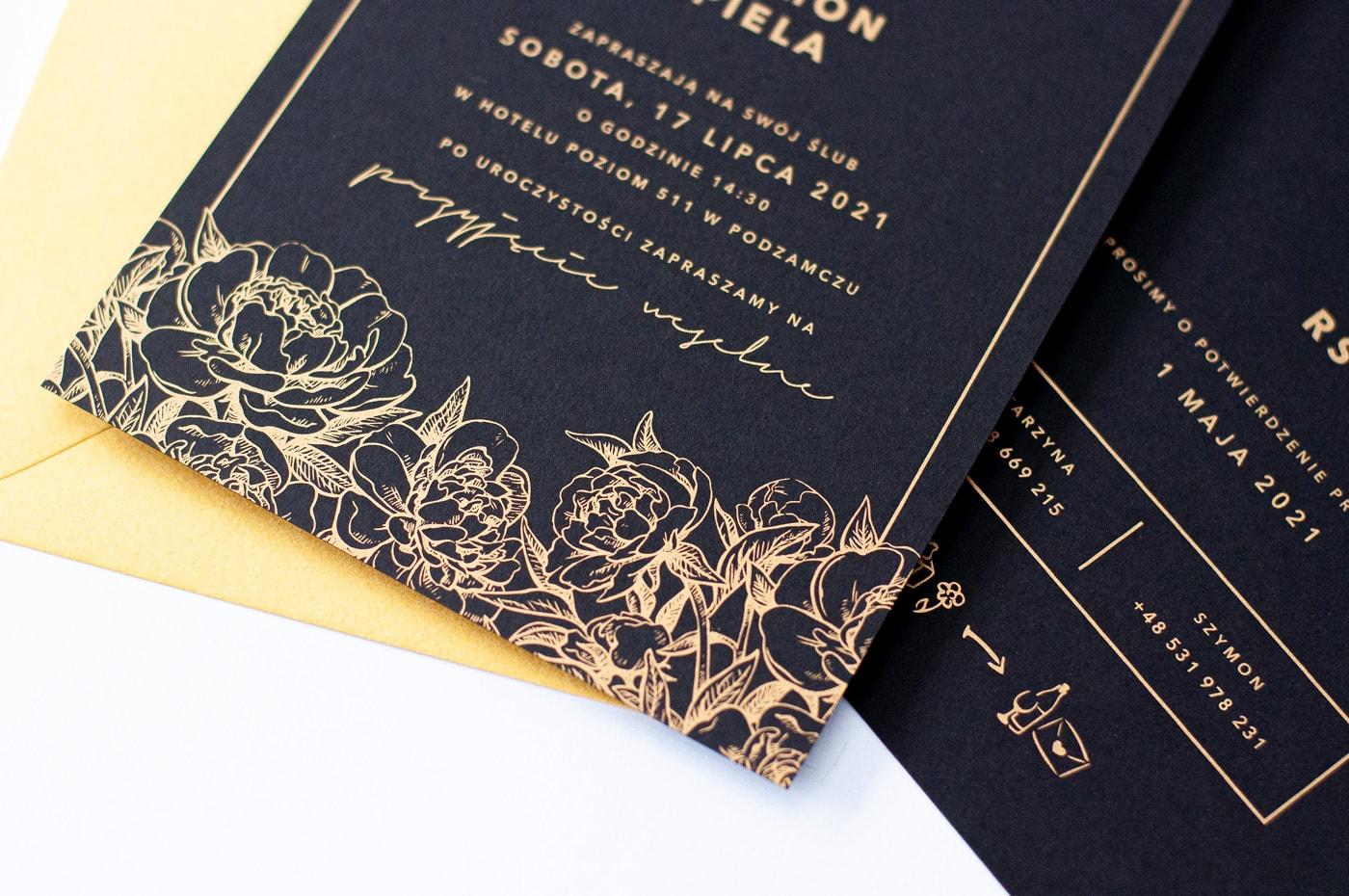 Czarne zaproszenia ze złotą kopertą i złotym drukiem piwonie