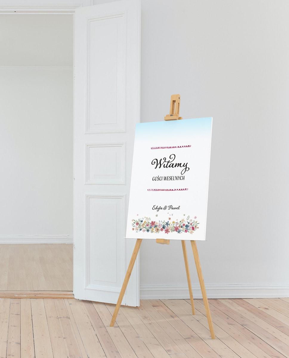 Rustykalna tablica powitalna z kompozycją polnych kwiatów na jasnoniebieskim tle