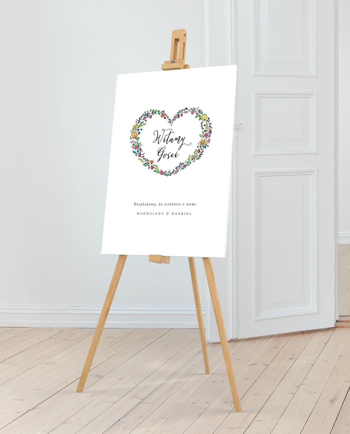 Tablica z powitaniem gości i imionami Pary Młodej w sercu z kwiatów