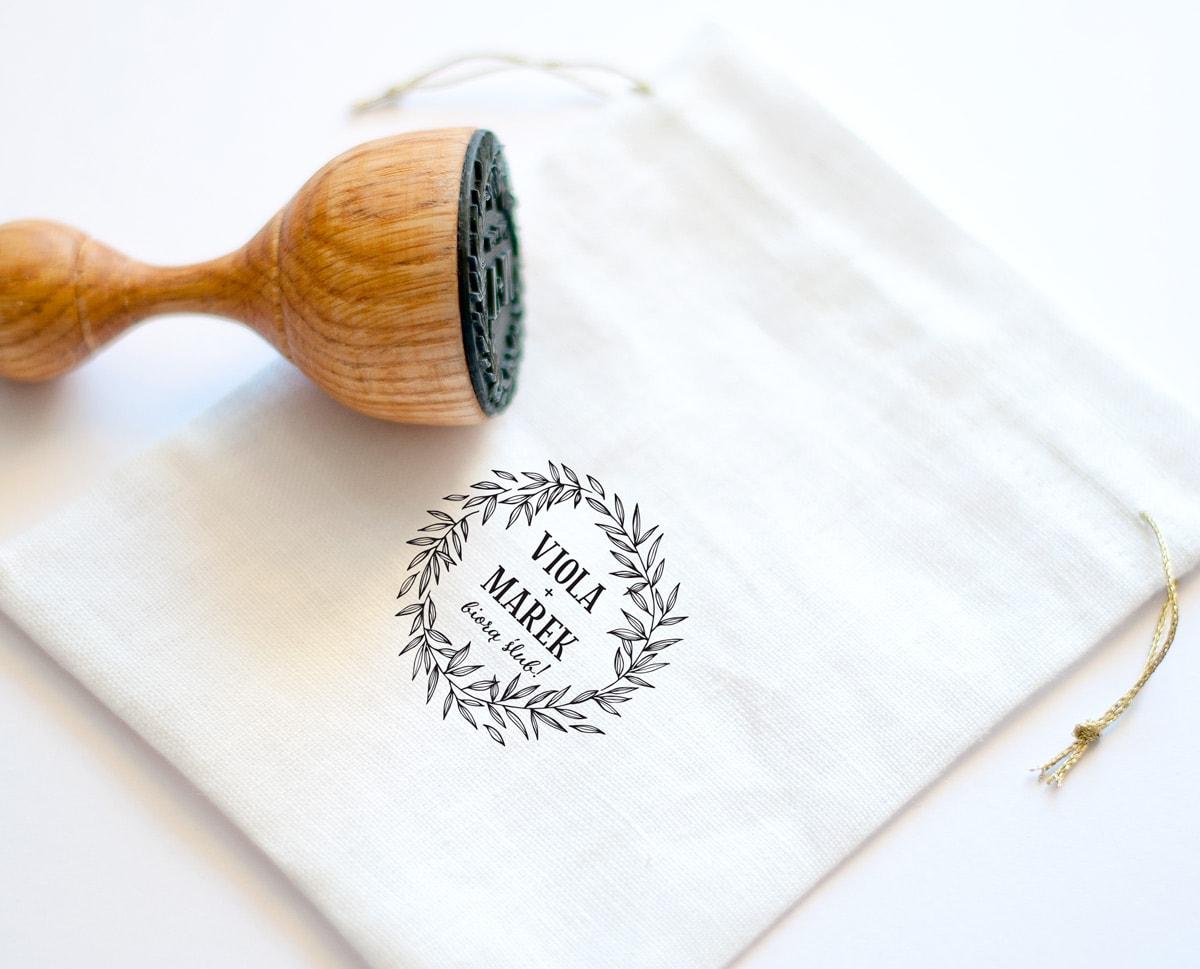 Biały lniany woreczek ze złotym sznureczkiem i drewnianą pieczątką