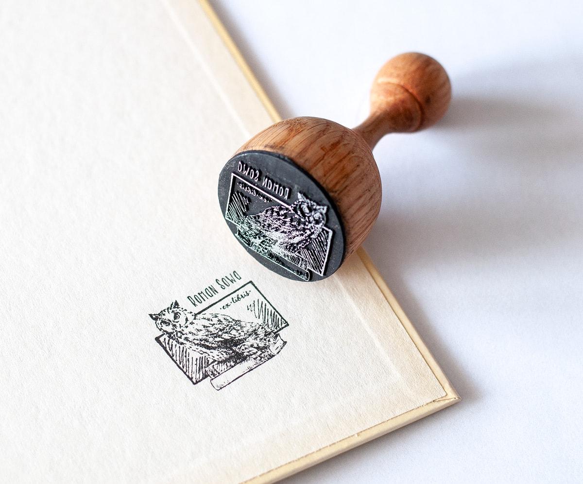 Pieczątka ekslibris z wizerunkiem sowy na książce
